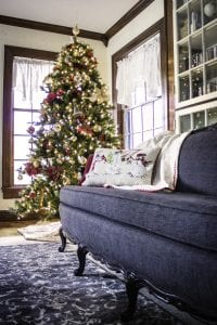 Decorated Christmas tree next to sofa in corner of room by windows.