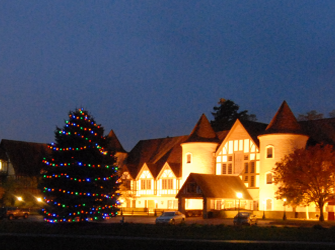 large building lit with lights with lighted Christmas trees