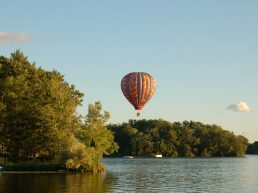 hot air balloon flying over lake