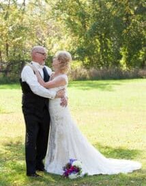 bride and groom hugging on lawn