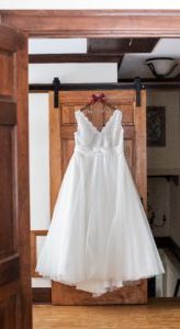 brides dress hung on door