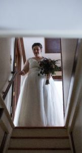 bride holding bouquet at top of stairs, descending for her wedding