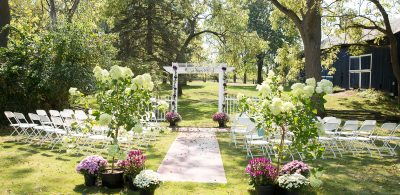 setup for a wedding on a beautiful day, with flowers, white chairs and a gazebo