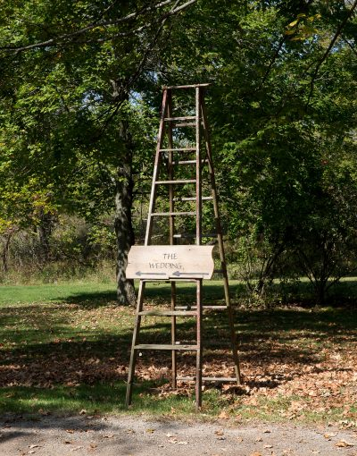 ladder with sign pointing to ceremony site