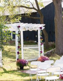 White arbor at ceremony site decorated with pink flowers