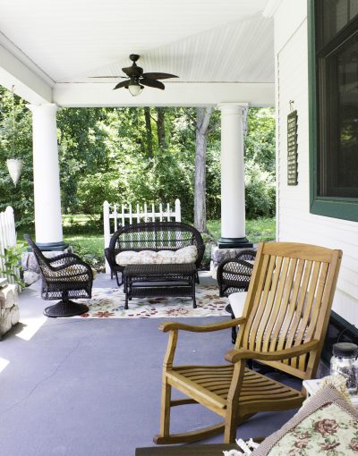 The porch is filled with several type of chairs for a relaxing visit.
