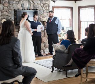bride and groom getting married in front of stone fireplace with guests looking on