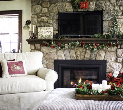 chair next to blazing fireplace, with Christmas decor