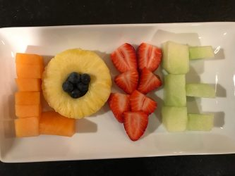 fresh fruit arranged on plate to spell LOVE