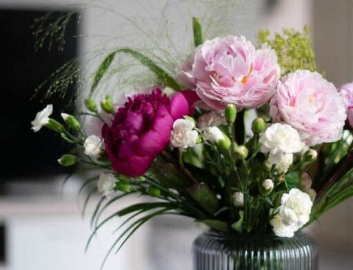 pink and white flowers in a clear vase on a round table