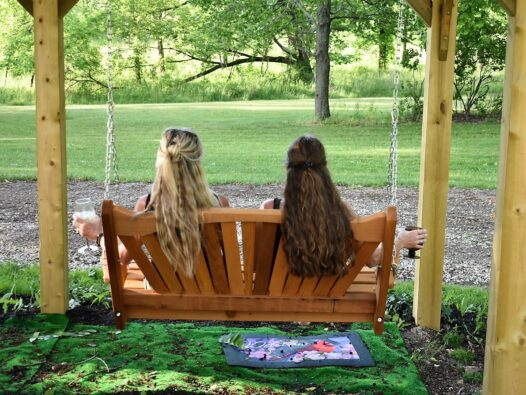 two ladies with long hair sitting on swing