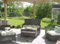 Outdoor patio area has several chairs for sitting.