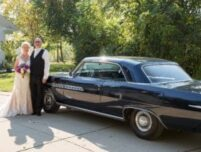 bride and groom standing next to blue car