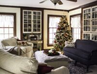 Decorated Christmas tree near sofas and chairs in corner of room by windows.